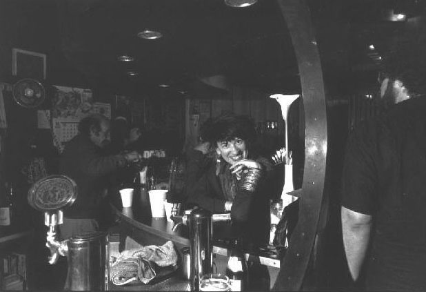 """Cafe Babar front room in the evening. Visible are Anna Wolfe, David Lerner (right) and Alvin Stillman (proprietor, who as Lerner once wrote, """"...will surely be a saint in heaven, as he is now in hell)."""" Photo by Richard Gibson."""